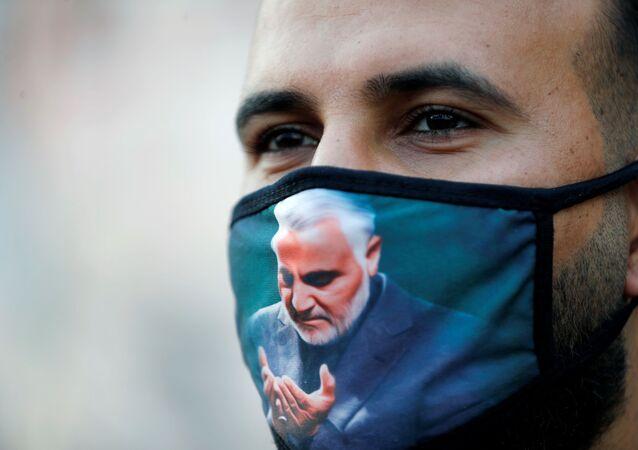 Homem usa máscara protetora com a imagem do general iraniano Qassem Soleimani, em Bagdá, Iraque, 3 de janeiro de 2020