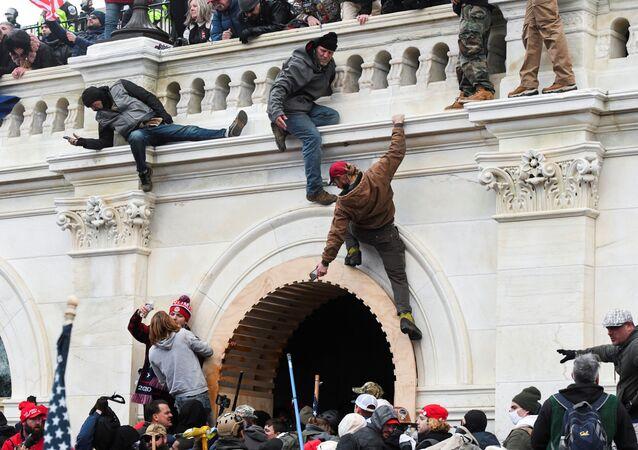 Apoiadores do presidente dos Estados Unidos, Donald Trump, sobem pelas paredes do Capitólio dos EUA durante o protesto contra a certificação dos resultados das eleições presidenciais de 2020 pelo Congresso, Washington, EUA, 6 de janeiro de 2021