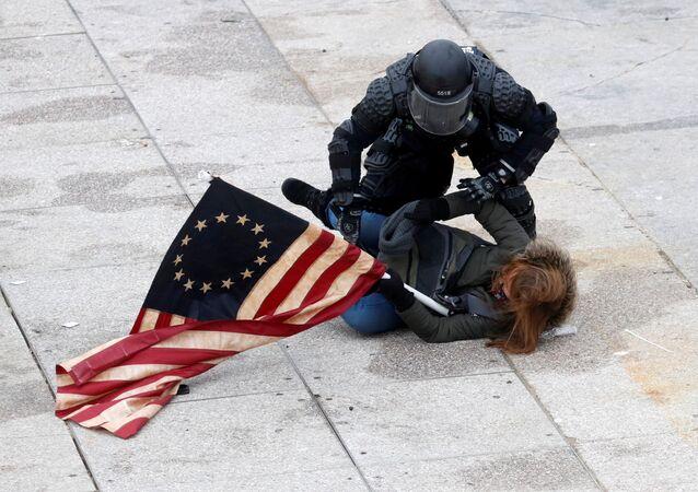 Policial imobiliza manifestante favorável a Donald Trump na frente da sede do Congresso dos EUA, Washington, 6 de janeiro de 2021