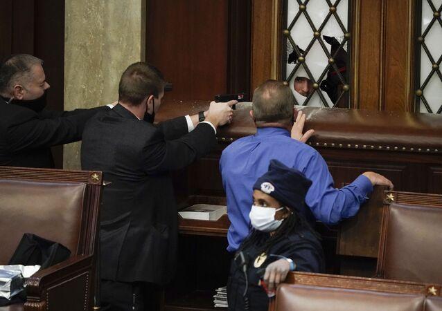 Policiais armados vigiam os manifestantes que tentam invadir a Câmara dos Representantes no Capitólio dos EUA em Washington, EUA, 6 de janeiro de 2021