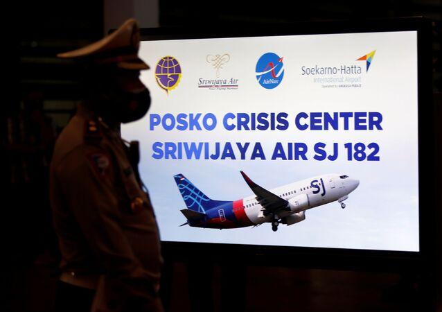 Policial passa em frente ao monitor do comitê de crise temporário instalado após o avião da Sriwijaya Air cair na Indonésia.