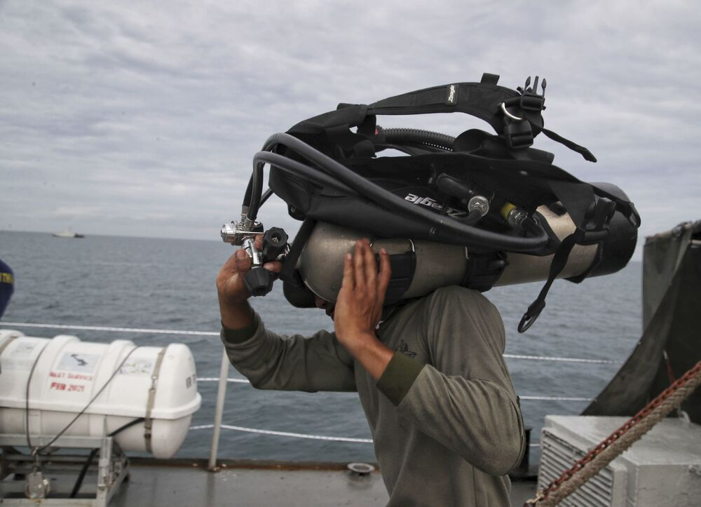 Mergulhador se prepara para imergir no local do acidente no mar de Java