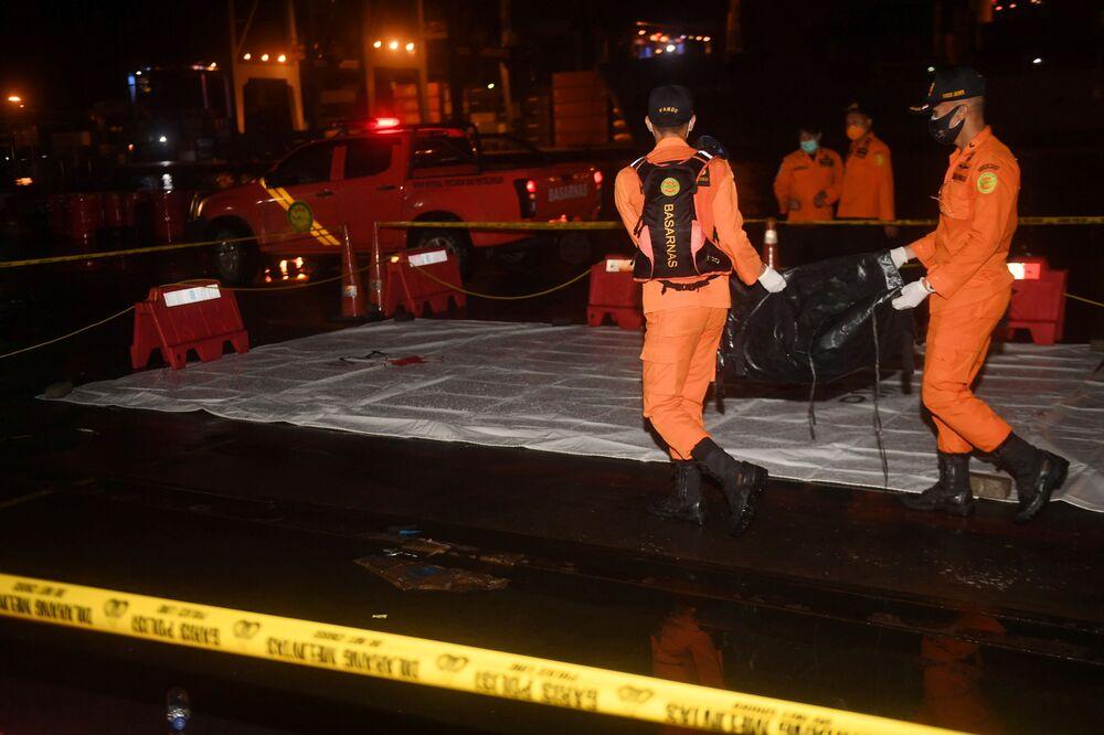 Socorristas levam corpos das vítimas do acidente aéreo no mar de Java