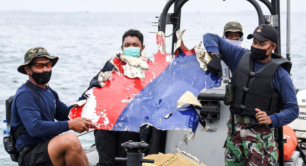Membros da Marinha indonésia carregam destroços do Boeing 737-500 da Sriwijaya Air, na costa da ilha de Java, em 10 de janeiro de 2021