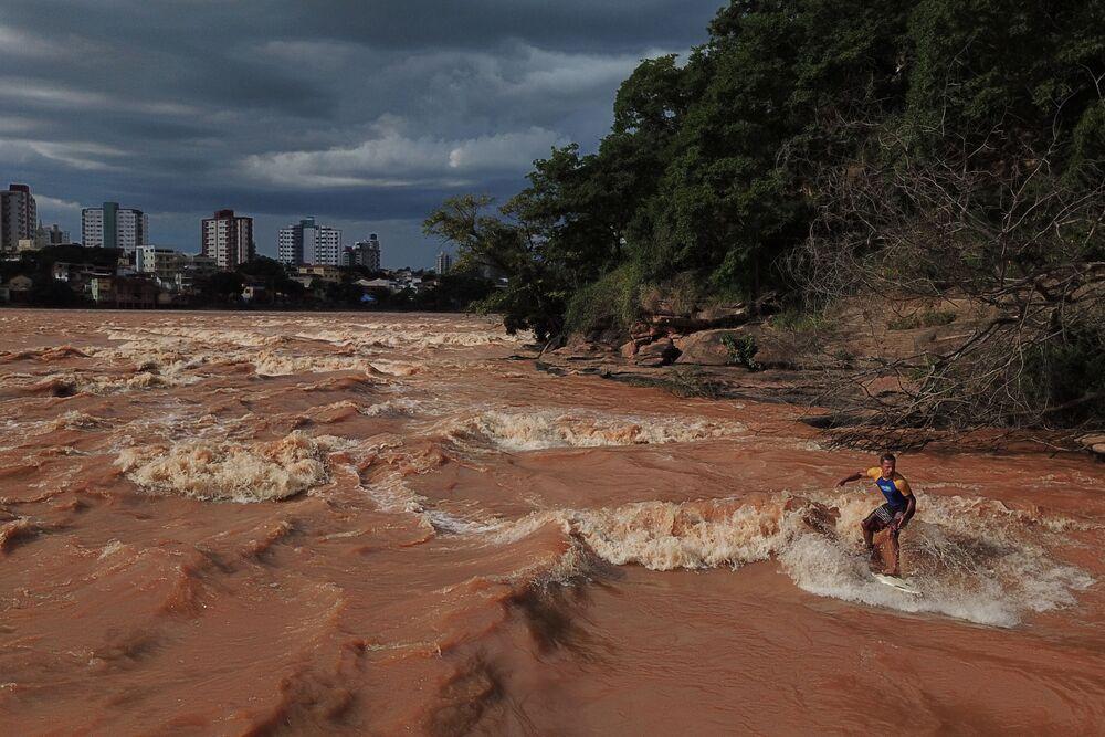 Surfista Paulo Guido se equilibra em cima de prancha de surfe no rio Doce em Governador Valadares, MG