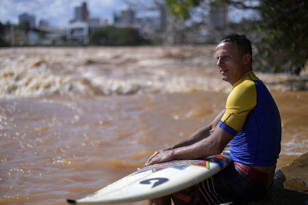 Surfista Paulo Guido observa ondas no rio Doce, em Governador Valadares, em estação de chuvas em Minas Gerais
