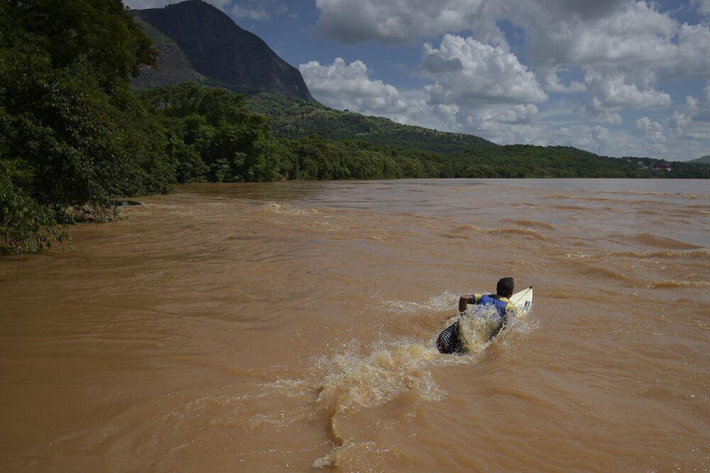 Surfista Paulo Guido se prepara para surfar em ondas do rio Doce em Governador Valadares, Minas Gerais