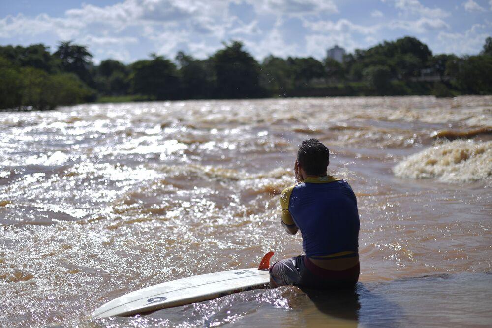 Paulo Guido, surfista brasileiro, é fotografado ao passo que ondas no rio Doce, na cidade mineira de Governador Valadares