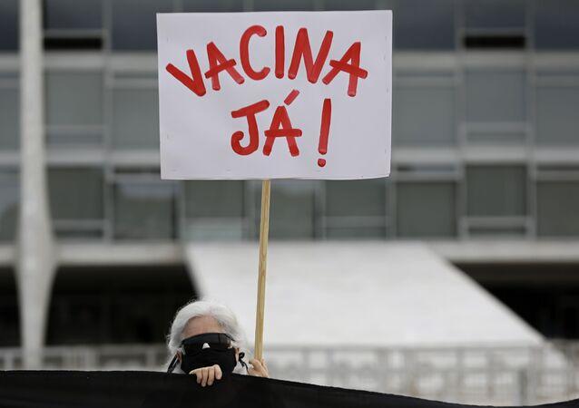 Manifestante protesta pelo início da vacinação contra a COVID-19 no Brasil, na frente do Palácio da Alvorada, Brasília, 8 de janeiro de 2021