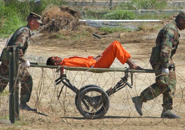 Na prisão de Guantánamo, militares americanos transportam prisioneiro para ser interrogado