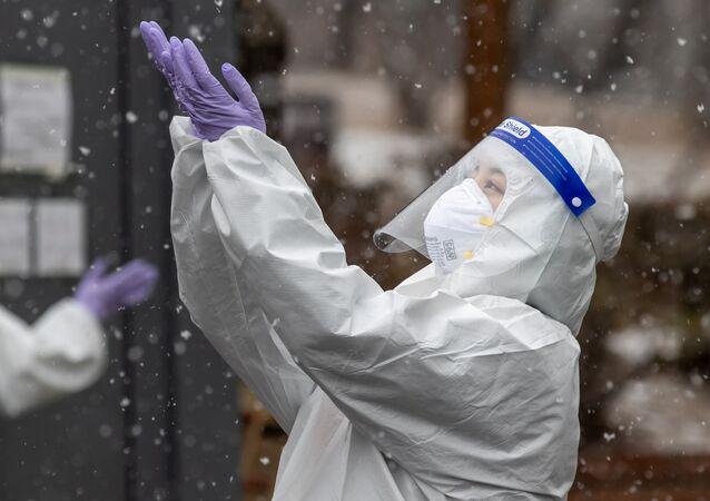 Médico vestindo macacão de proteção desfruta da neve caindo em local de testes para a COVID-19, Seul, Coreia do Sul, 12 de janeiro de 2021