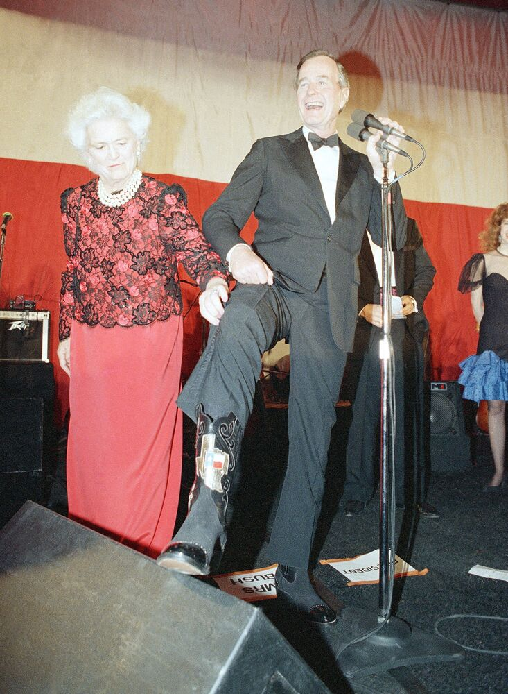 Primeira-dama Barbara Bush ajuda seu marido, o presidente George H. Bush, a mostrar uma bota com emblema do estado do Texas durante uma recepção com gravata preta e botas do Texas em Washington, Estados Unidos, 21 de janeiro de 1989