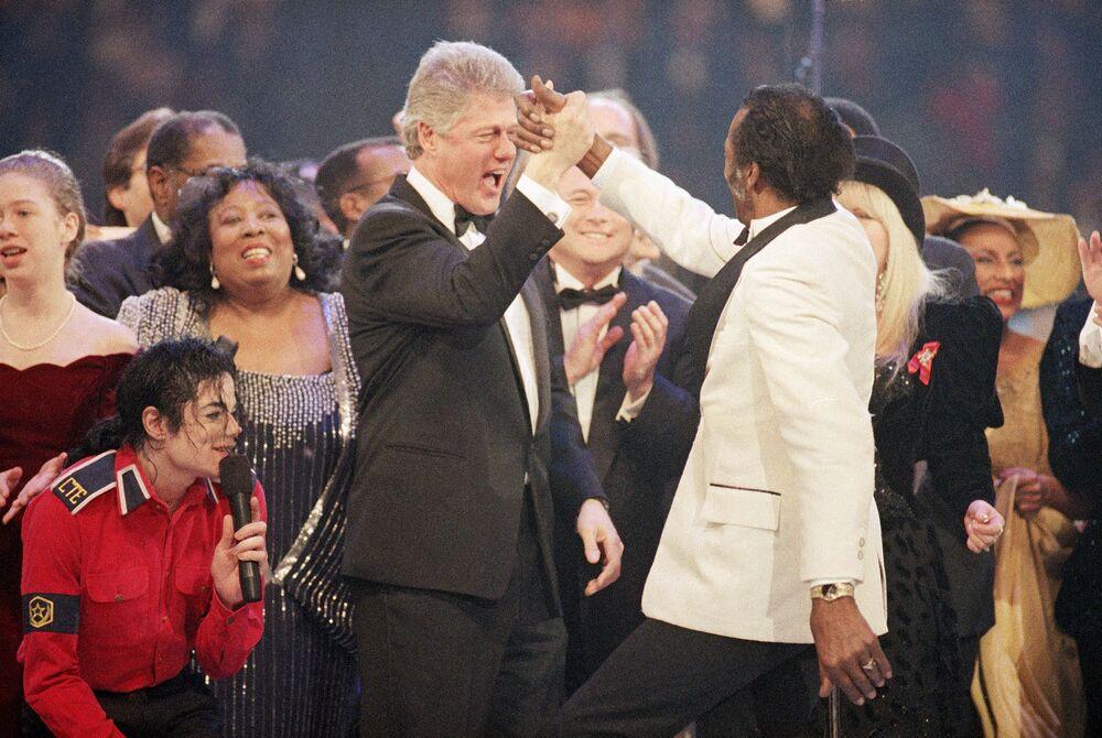Presidente eleito Bill Clinton, à esquerda ao centro, dá um toque de cumprimento a Chuck Berry, à direita, durante o final da Gala Presidencial no Capital Centre em Landover, estado de Maryland, Estados Unidos, 19 de janeiro de 1993. À esquerda estão Michael Jackson, agachado, e Chelsea Clinton