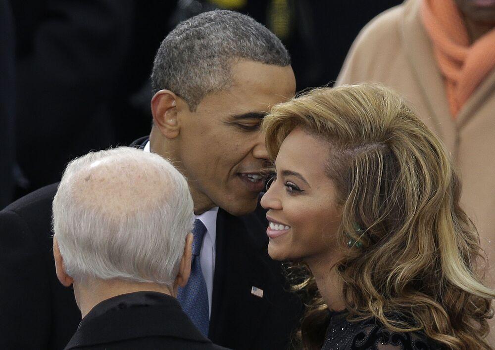 Presidente Barack Obama fala com a cantora Beyonce antes de ela cantar o hino nacional durante sua cerimônia de posse como 57º presidente dos EUA, em Washington, 21 de janeiro de 2013
