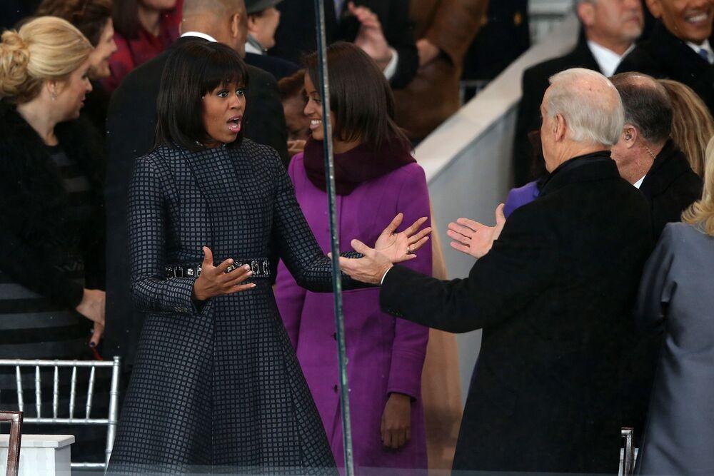 Primeira-dama Michelle Obama cumprimenta o vice-presidente Joe Biden durante o desfile de posse em Washington, EUA, em 21 de janeiro de 2013. Barack Obama prestou juramento para o segundo mandato como presidente dos EUA