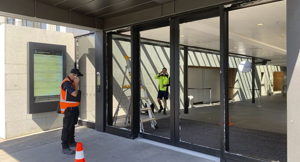 Funcionários do Parlamento da Nova Zelândia inspecionam as portas da frente quebradas na quarta-feira, 13 de janeiro de 2021, em Wellington, Nova Zelândia. A polícia disse que um homem armado com um machado quebrou as portas de vidro, mas não tentou entrar no prédio.