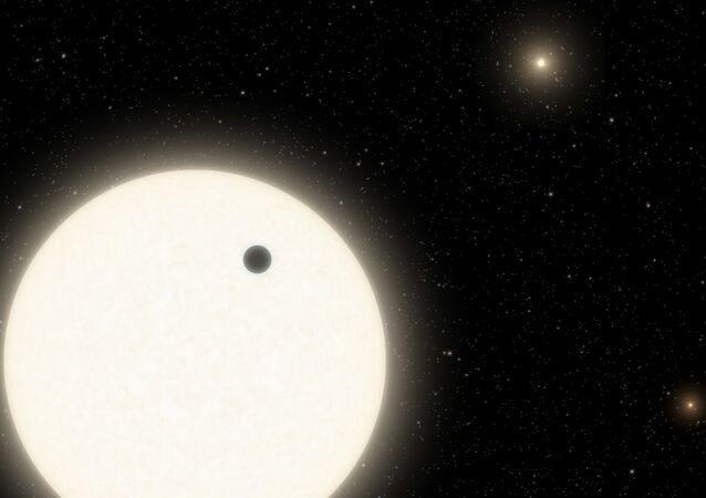 Ilustração do planeta KOI-5Ab transitando através de uma estrela similar ao Sol, que faz parte do sistema estelar triplo