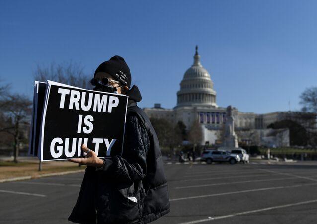 Manifestante contrário ao presidente Donald Trump segura, em frente ao Capitólio dos EUA, placa que diz: Trump é culpado. Foto tirada em Washington, no dia 13 de janeiro de 2021.