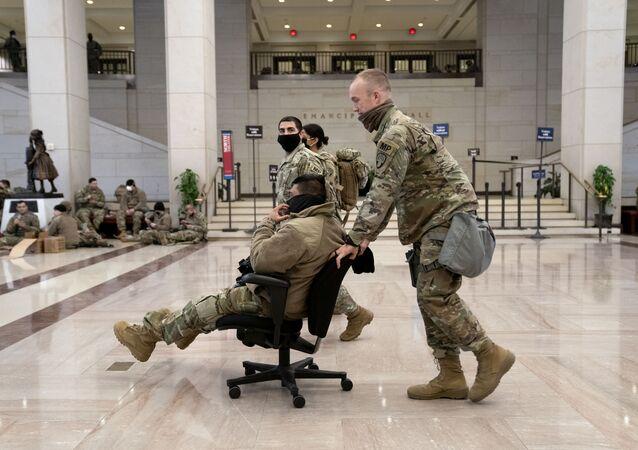 Membro da Guarda Nacional empurra colega em cadeira de rodinhas no Centro de Visitantes no Capitólio dos EUA, Washington, 13 de janeiro de 2021. A segurança foi reforçada devido à invasão do Capitólio em 6 de janeiro e à tomada de posse de 20 de janeiro