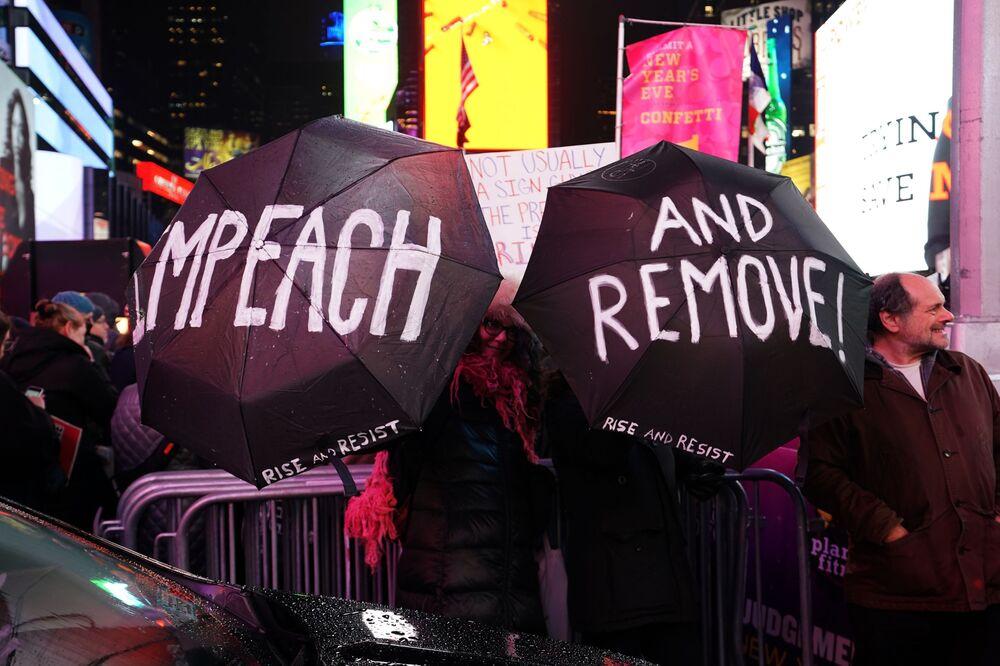Mais de mil manifestantes se reúnem na Times Square, 17 de dezembro de 2019, a favor do impeachment do presidente norte-americano. No primeiro pedido de impeachment, Donald Trump foi acusado de pressionar o novo presidente da Ucrânia, Vladimir Zelensky, para que as autoridades ucranianas investigassem a interferência de Joe Biden e seu filho Hunter nas eleições presidenciais de 2016