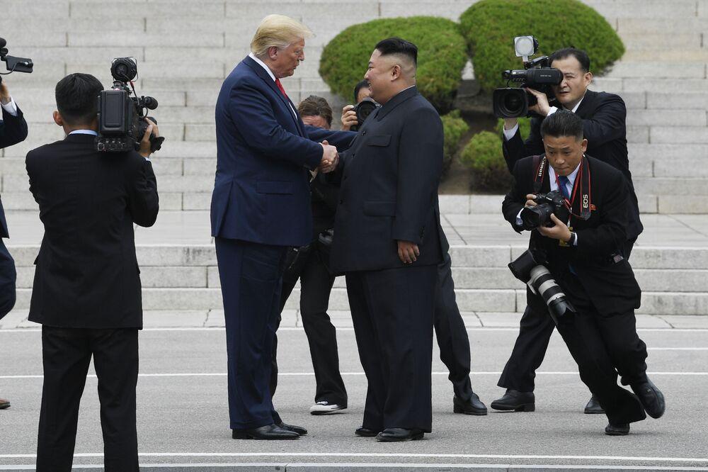 Presidente Donald Trump e o líder norte-coreano Kim Jong-un reúnem-se na aldeia fronteiriça de Panmunjom da zona desmilitarizada, na fronteira intercoreana, 30 de junho de 2019. Donald Trump tornou-se o primeiro presidente norte-americano a pisar em território da Coreia do Norte