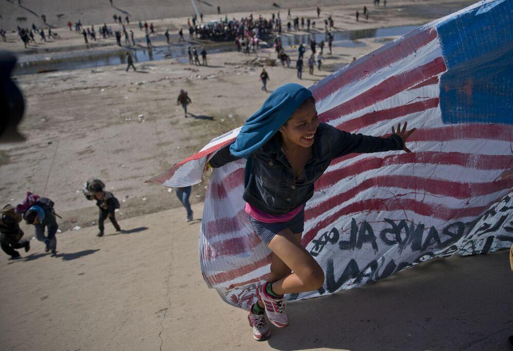 Imigrante ajuda a levar a bandeira norte-americana à fronteira entre o México e os EUA, depois de ter ultrapassado a polícia mexicana na fronteira. A construção de um muro fronteiriço entre os EUA e o México mais fortificado foi uma das promessas da campanha eleitoral de Trump de 2016