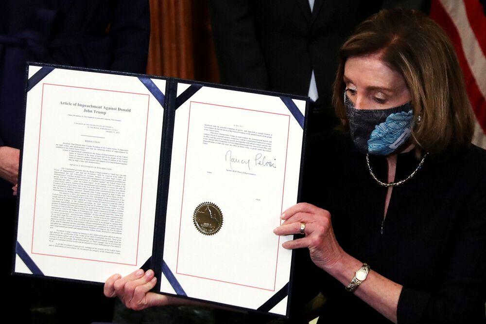 Presidente da Câmara dos Representantes, Nancy Pelosi mostra artigo assinado de impeachment contra o presidente Donald Trump, no Congresso em Washington, 13 de janeiro de 2021