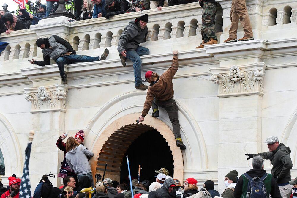 Trumpistas escalam as paredes do Capitólio durante protestos contra certificação dos resultados da eleição presidencial no Congresso norte-americano, em Washington, 6 de janeiro, 2021