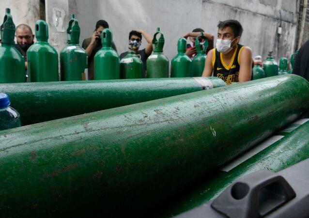 Parentes de pacientes internados em hospitais com COVID-19 fazem fila para recarregar cilindros de oxigênio na frente da empresa Nitron da Amazônia, no Distrito Industrial II de Manaus (AM)