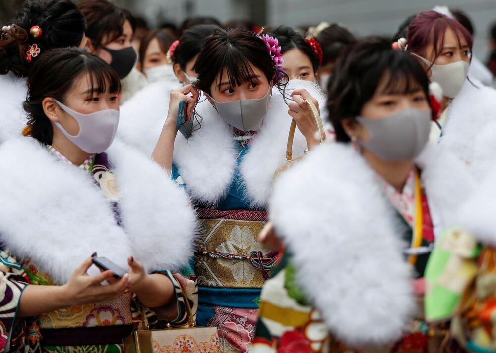 Meninas usando quimonos e máscaras de proteção durante a cerimônia de celebração de chegada da idade adulta, Tóquio, 11 de janeiro de 2021