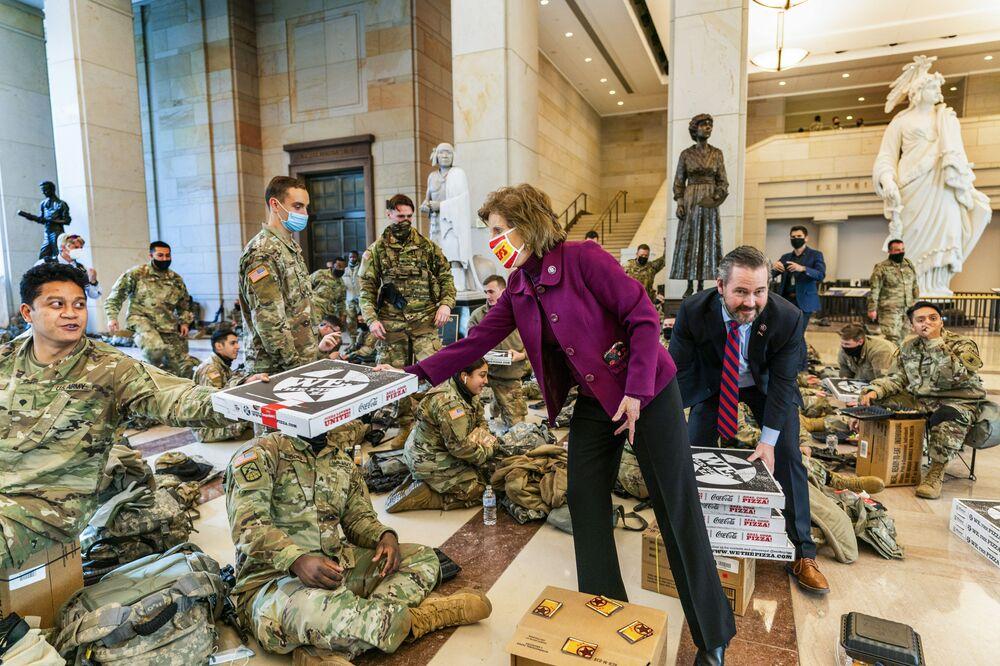 Republicanos da Câmara dos Representantes Vicky Hartzler e Michael Waltz entregam pizzas para os membros da Guarda Nacional no Centro de Visitantes no Capitólio, Washington, EUA, 13 de janeiro de 2021. A Câmara dos Representantes continua sua votação rápida sobre o impeachment do presidente Donald Trump
