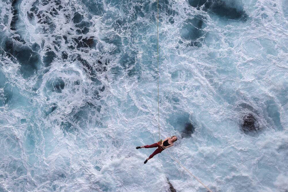 Mulher balança em uma corda sobre o oceano após saltar de penhasco perto de Currarong, Austrália, 9 de janeiro de 2021