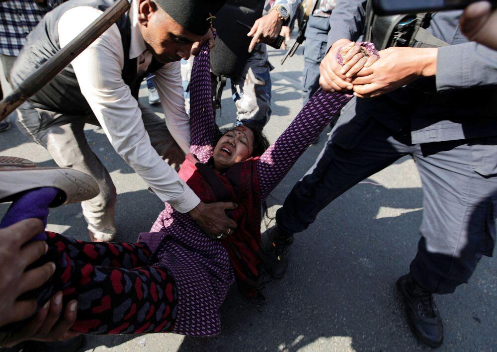 Apoiador da monarquia é ajudado após ter sido ferido durante confrontos com a polícia de choque, Catmandu, Nepal, 11 de janeiro de 2021