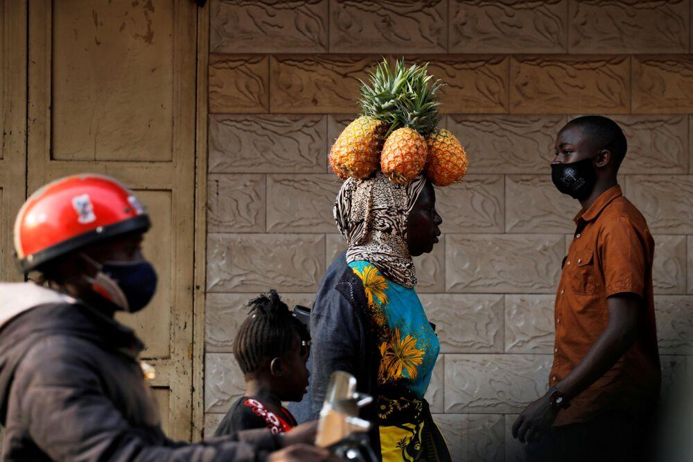 Mulher leva abacaxis na cabeça em rua de Campala, Uganda, 12 de janeiro de 2021