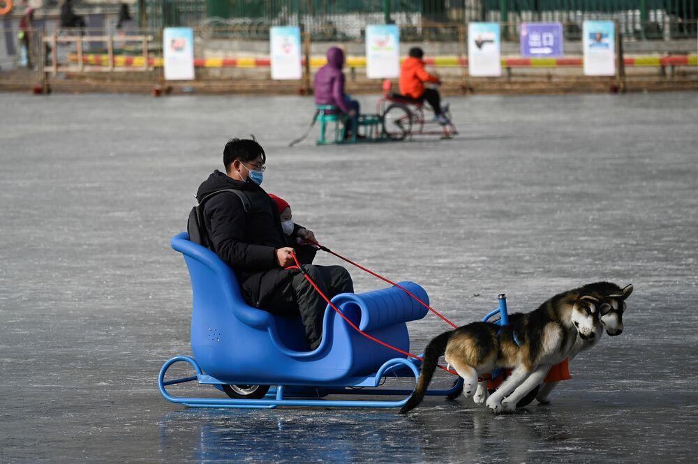 Homem e criança usam trenó em lago congelado em Pequim, China, 12 de janeiro de 2021