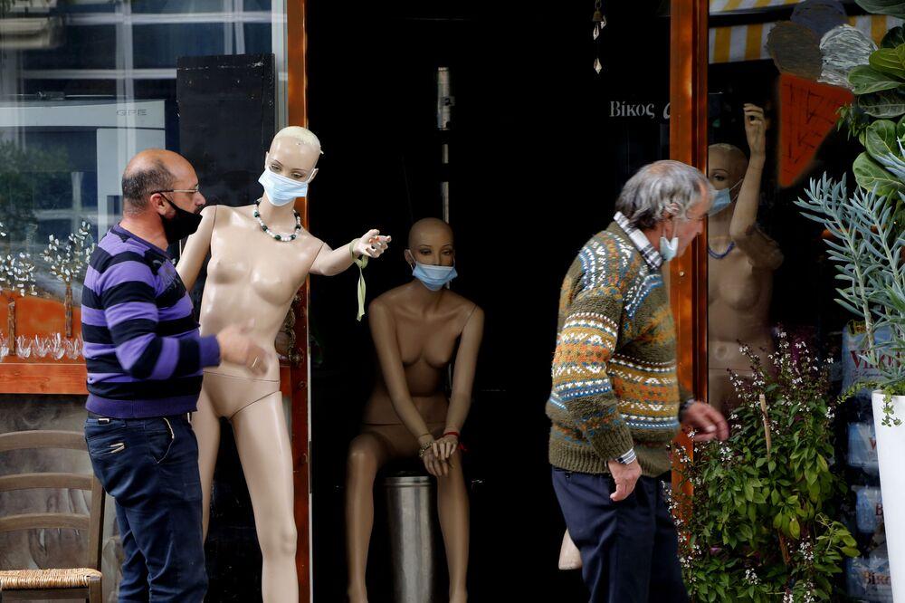 Dono de loja leva um manequim nu, mas com máscara, em Nicósia, Chipre, 11 de janeiro de 2021