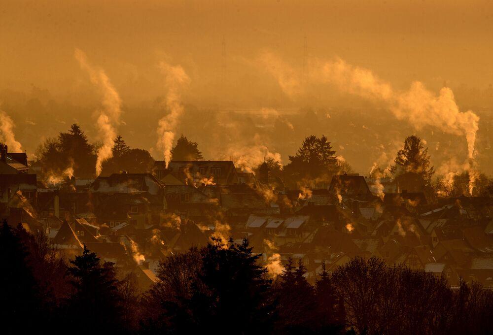 Vapor sobe de casas enquanto o sol nasce na cidade de Kronberg, perto de Frankfurt, Alemanha, 11 de janeiro de 2021