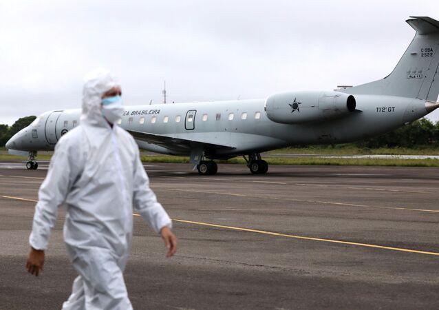 Agente da saúde perto de um avião da Força Aérea Brasileira antes de este decolar com pacientes com COVID-19 em Manaus, Brasil, 15 de janeiro de 2021