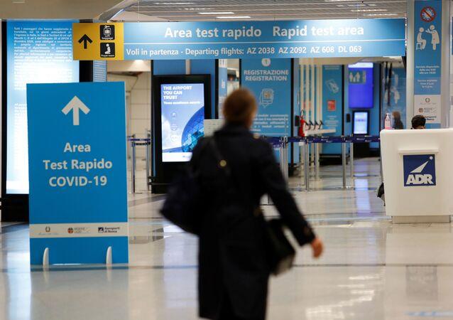 Uma pessoa caminha ao lado de uma área de testagem contra COVID-19 no Aeroporto Internacional Leonardo da Vinci, em Roma.