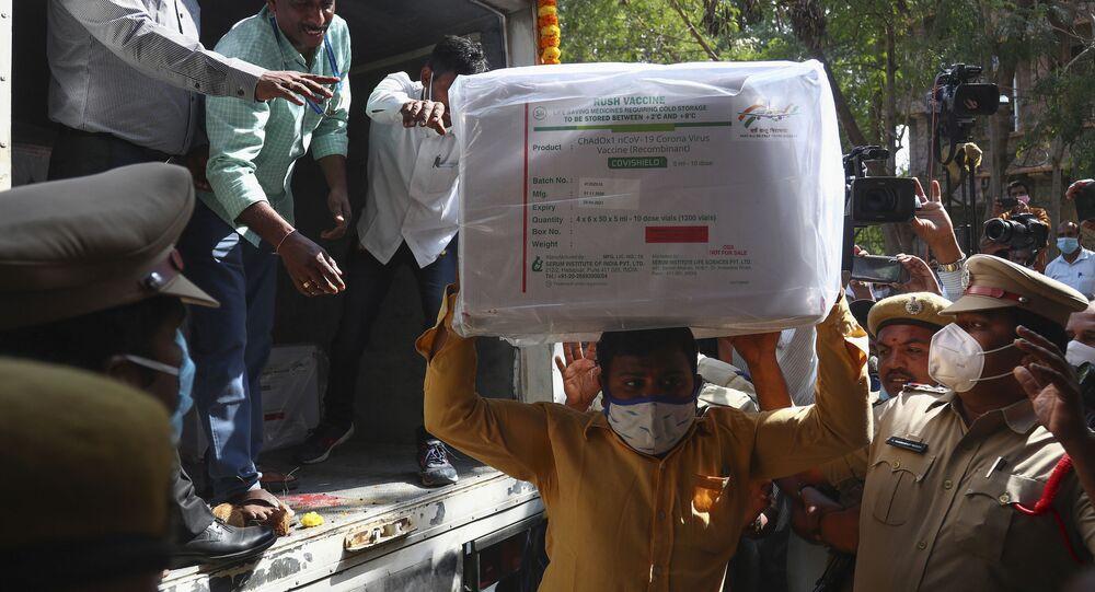 Em Hyderabad, na Índia, em meio à preparação para a campanha de imunização no país asiático, profissionais de saúde desembarcam caixas com a vacina contra a COVID-19, em 12 de janeiro de 2021