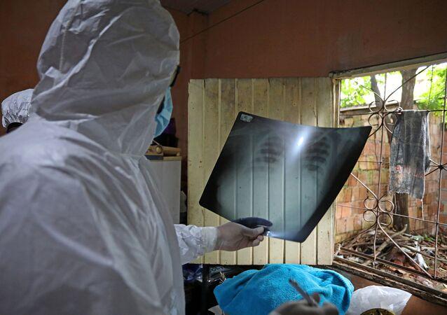Trabalhadores da saúde examinam raio X de mulher de 53 anos que morreu com sintomas da COVID-19 em Manaus, Brasil, 11 de janeiro de 2021