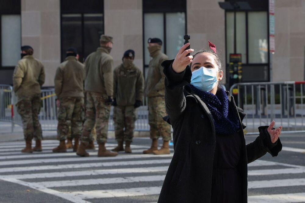 Mulher tira selfie na frente de soldados da Guarda Nacional em Washington, Estados Unidos, 17 de janeiro de 2021