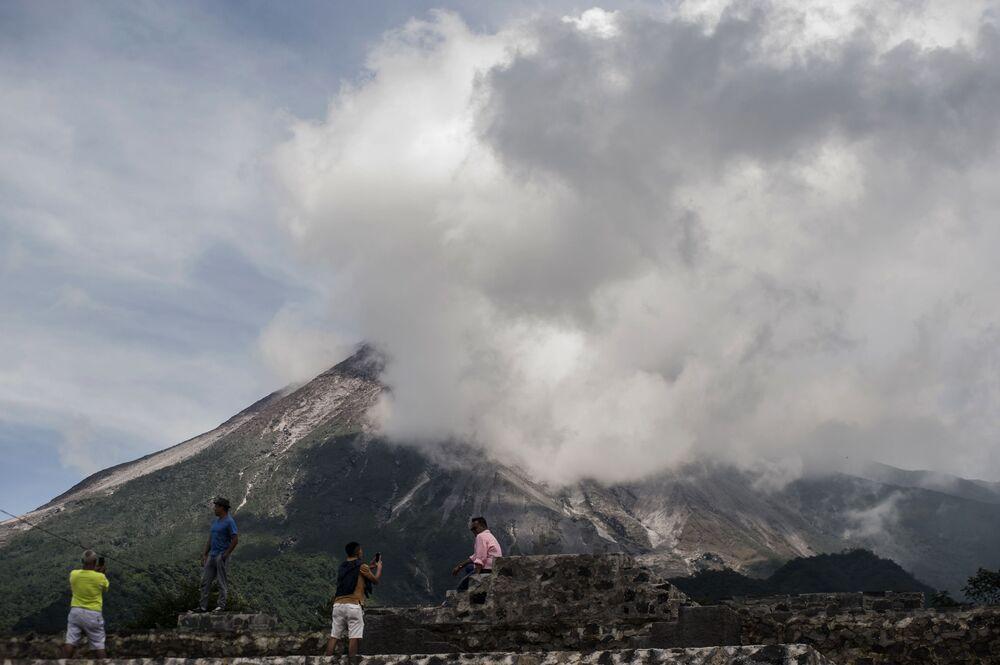 As pessoas assistem o vulcão mais ativo da Indonésia, o Monte Merapi, expelir rochas e gás em Yogyakarta, em 17 de janeiro de 2021