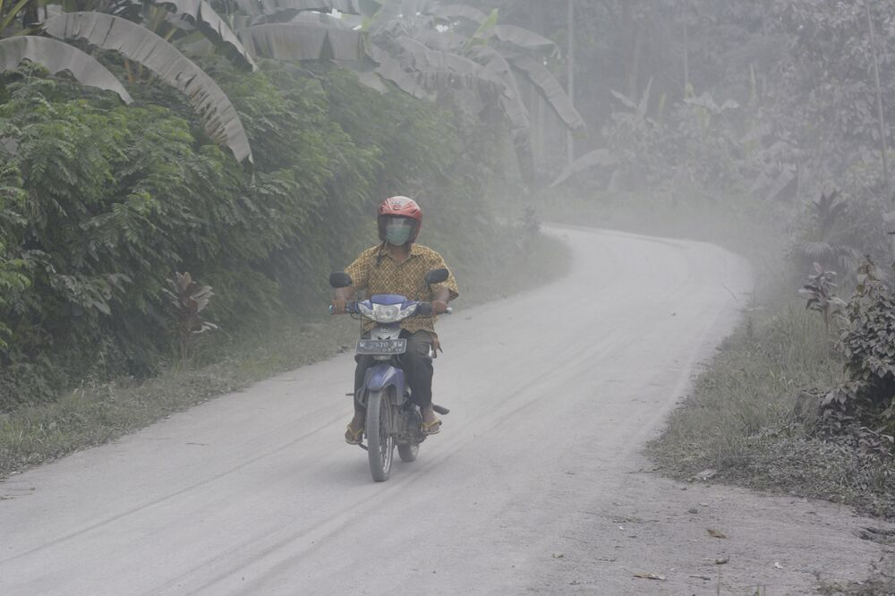 Motociclista passa por estrada coberta de cinzas vulcânicas da erupção do Monte Semeru, na ilha de Java, Indonésia, em 17 de janeiro de 2021