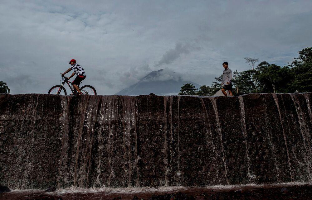 Moradores passam pelo Monte Semeru, na ilha de Java, Indonésia, em 17 de janeiro de 2021, um dia após a erupção do vulcão
