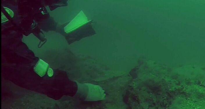 Mergulhadores da equipe NorthSeaDivers perto de navio naufragado
