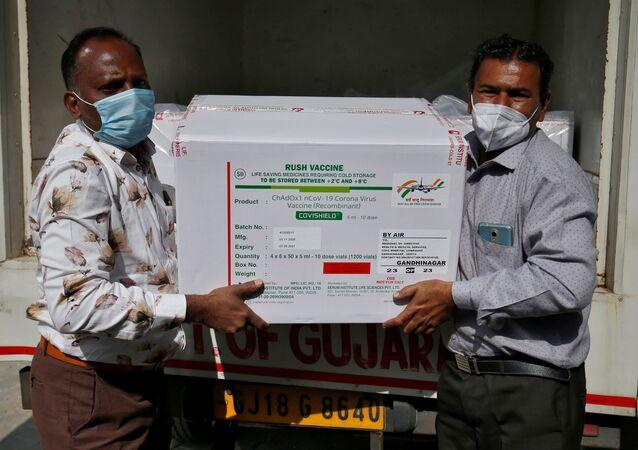 Funcionários descarregam caixas com vacina desenvolvida pela AstraZeneca e produzida no instituto Serum, na Índia