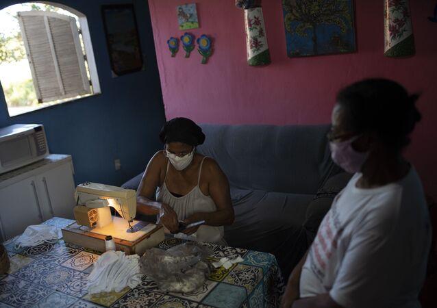 No Rio de Janeiro, duas quilombolas costuram máscaras de proteção contra a COVID-19 no quilombo Maria Joaquina, em Cabo Frio, em 12 de julho de 2020