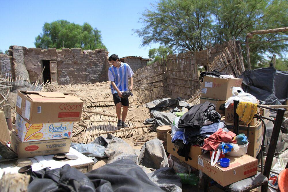 Adolescente recupera objetos dentre escombros de sua casa destruída pelo terremoto na província argentina de San Juan em 18 de janeiro de 2021