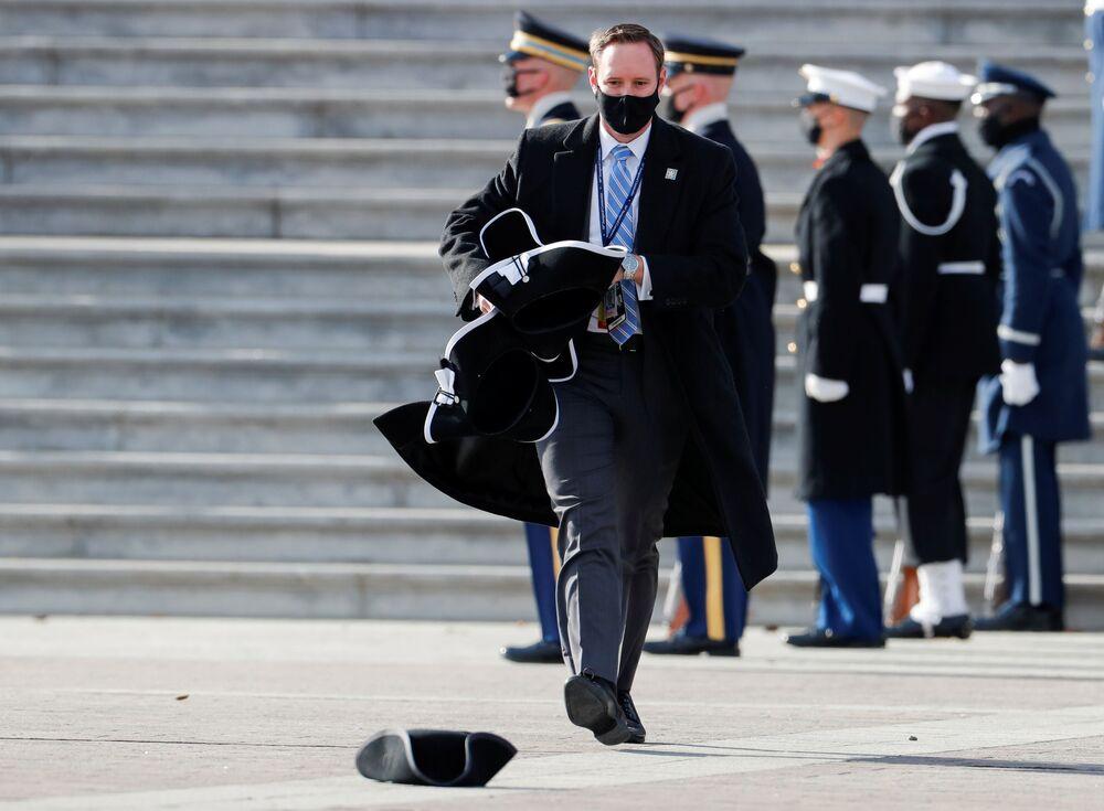 Funcionário junta chapéus após cerimônia de posse de Joe Biden como 46º presidente dos EUA, 20 de janeiro de 2021